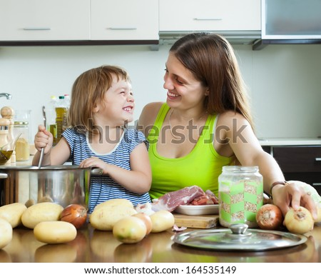 Happy woman with baby cooking   at home kitchen - stock photo