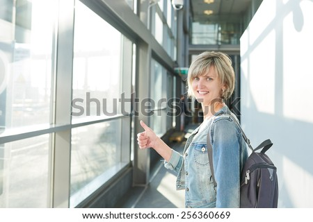 Happy woman with backpack standing in airport building going on boarding, gesturing thumb up - stock photo