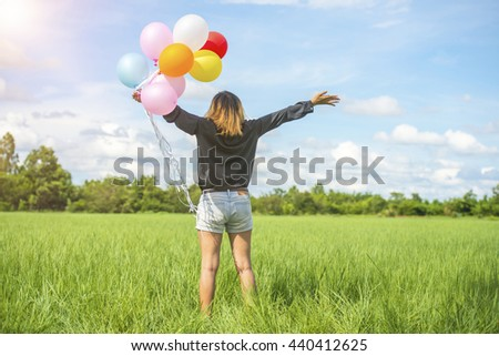 Happy Woman with balloons on the prairie