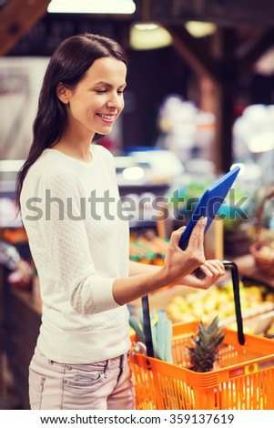 happy woman with basket and tablet pc in market - stock photo