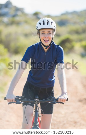 Happy woman with bike smiling at camera - stock photo