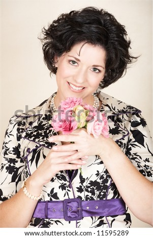 Happy woman with black curly in black and white fashion jacket, holding spring flowers in pink and green, mid 30s, early 40s - stock photo