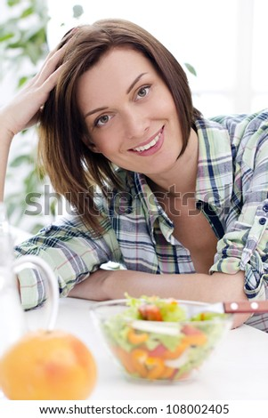 Happy woman with bowl of fresh and healthy salad - stock photo