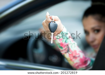Happy Woman with car keys, female driver holding car keys driving her new car. Luxury car and girl.  - stock photo