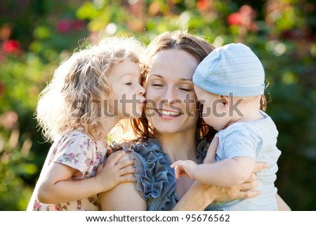 Happy woman with child and baby outdoors in spring garden - stock photo