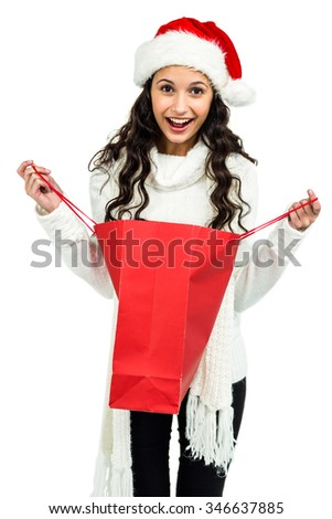 Happy woman with christmas hat opening red shopping bag on white screen - stock photo