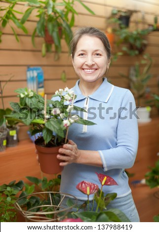 Happy  woman with Clerodendrum surrounded by different flowers in flower store - stock photo