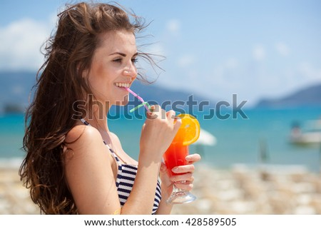 Happy woman with cocktail on the beach during tropical vacation