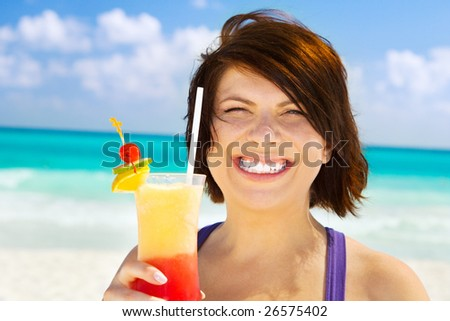 happy woman with colorful cocktail on the beach