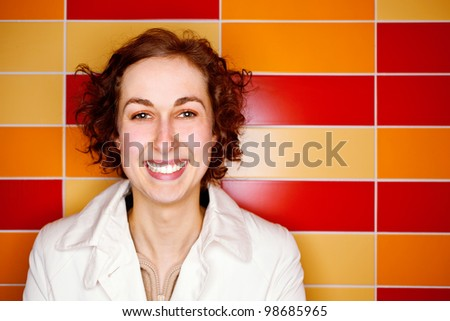 Happy woman with colorful tiles in the background - stock photo