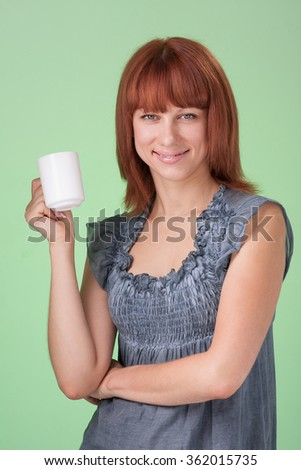 Happy woman with cup of tea or coffee, on green background
