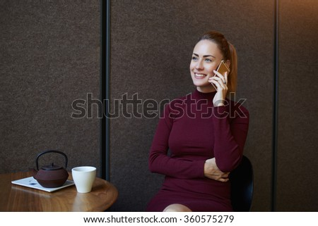 Happy woman with cute smile having a telephone conversation during coffee break in modern cafe bar interior, attractive female calling with mobile phone while waiting for her order at restaurant  - stock photo
