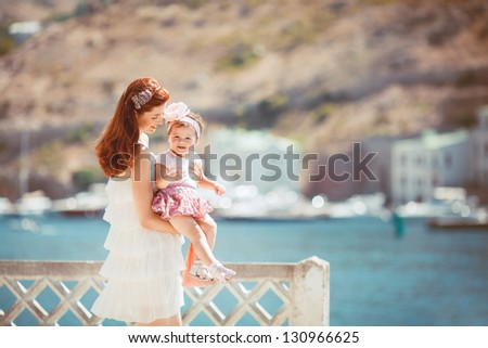 Happy woman with daughter resting at beach in summer outdoor