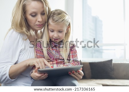 Happy woman with daughter using digital tablet in living room - stock photo