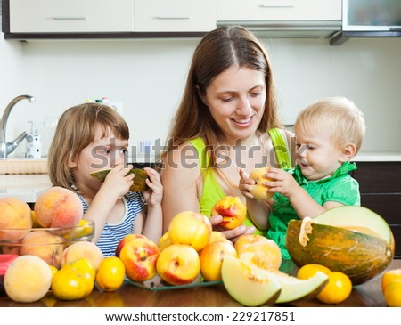 Happy woman with daughters together with melon and peaches over dining table