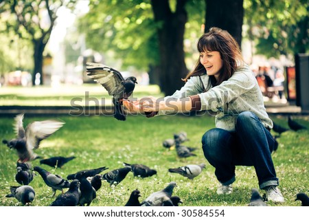 Happy woman with doves in park
