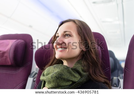 Happy woman with green scarf during flight in airplane - stock photo