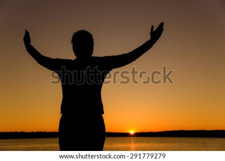 Happy woman with hands up at sunset or sunrise