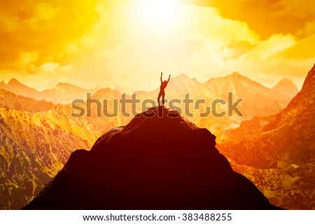 Happy woman with hands up on the peak of the mountain enjoying the success, freedom and bright future. - stock photo