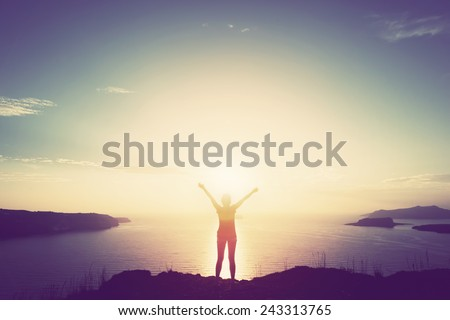 Happy woman with hands up standing on cliff over sea and islands at sunset. Vintage mood, concepts of winner, freedom, happiness etc. - stock photo