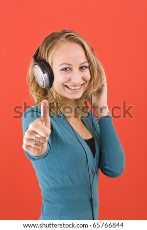 Happy woman with headphones, listen to music and showing sign ok. Isolated on red background - stock photo