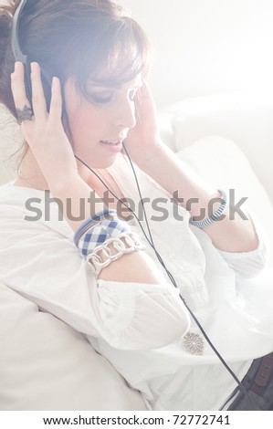 Happy woman with headphones lying down on sofa in lounge, listen to music - stock photo