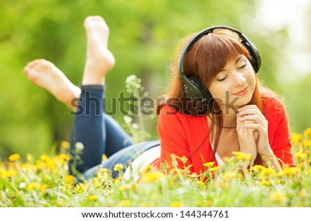Happy woman with headphones relaxing in the park - stock photo