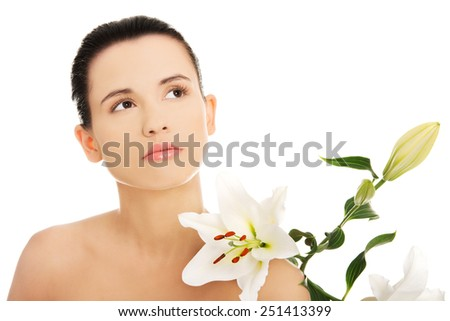 Happy woman with healthy skin and lily flower - stock photo