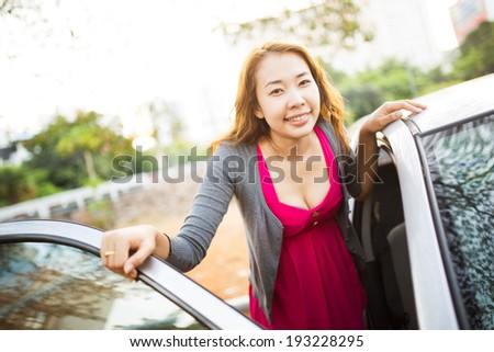 Happy woman with her car, door opened. - stock photo