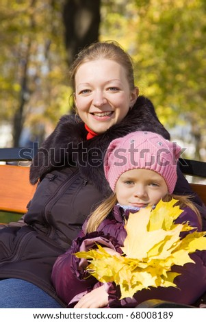 Happy woman with her daughter in autumn park