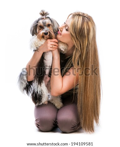 Happy woman with her dog Yorkshire Terrier in studio isolated on a white background
