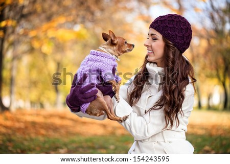 Happy woman with her little dog in autumn forest