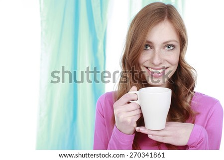 Happy woman with hot beverage in her hand smiling