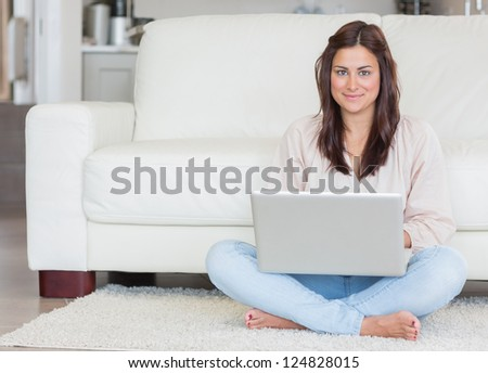 Happy woman with laptop on living room floor - stock photo