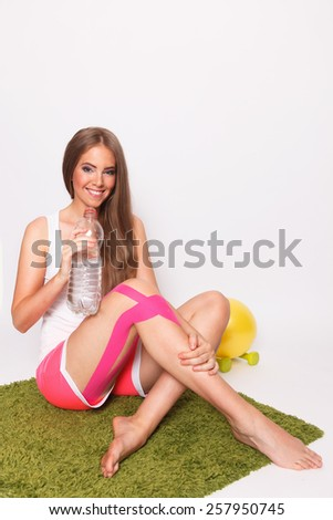 Happy woman with leg injury after workout - stock photo