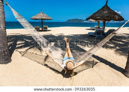 Happy woman with legs raised relaxing in a hammock