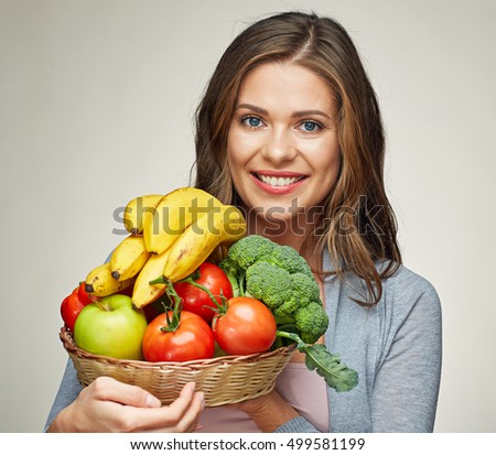 Happy woman with long hair and big toothy smile holding straw basket with healthy food fruits and vegetables.