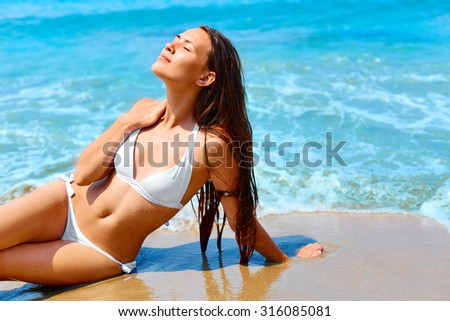 Happy woman with long hair and healthy glowing skin relaxing  on a beach in white bikini. - stock photo