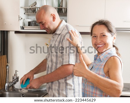 Happy woman with man washing plates in home kitchen - stock photo