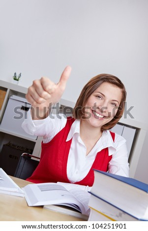 Happy woman with many books in office holding thumbs up - stock photo