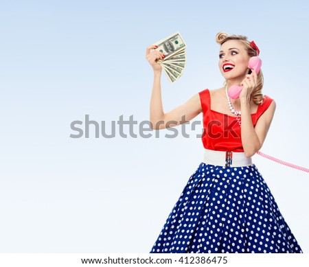 Happy woman with money, talking on phone, dressed in pin-up style dress in polka dot, on blue background, with blank copyspace area for text or slogan - stock photo