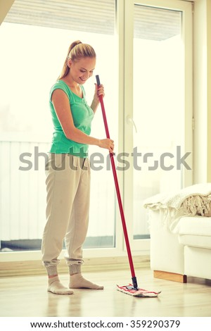 happy woman with mop cleaning floor at home - stock photo