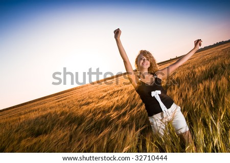 Happy woman with open arms in golden field of wheat - stock photo