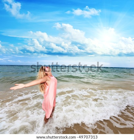 Happy woman with opened hands on the beach - stock photo