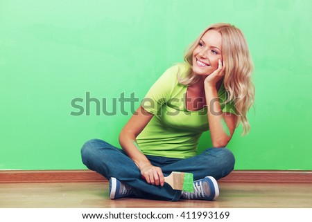 Happy woman with paint brush sitting near painted wall - stock photo