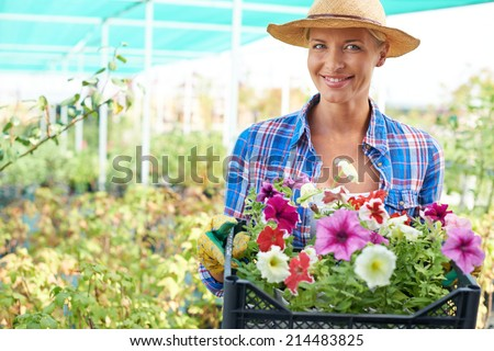 Happy woman with petunia flowers looking at camera - stock photo