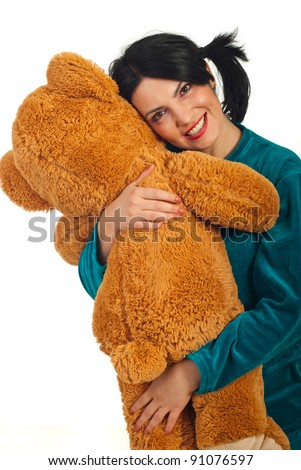Happy woman with pigtails wearing pajama and hugging big teddy bear toy isolated on white background - stock photo