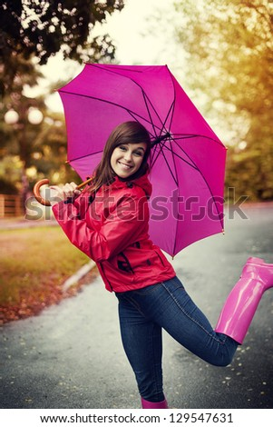 Happy woman with pink umbrella and rubber boots - stock photo
