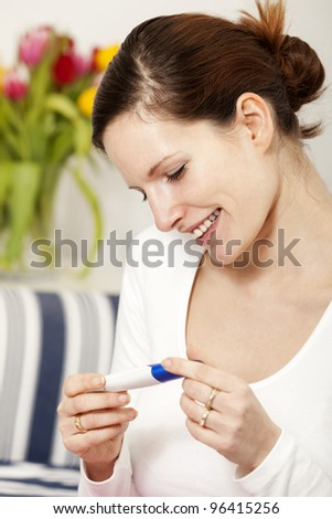 Happy woman with positive pregnancy test - stock photo