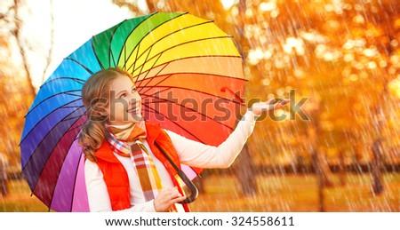 happy woman with rainbow multicolored umbrella under rain on nature in the park - stock photo